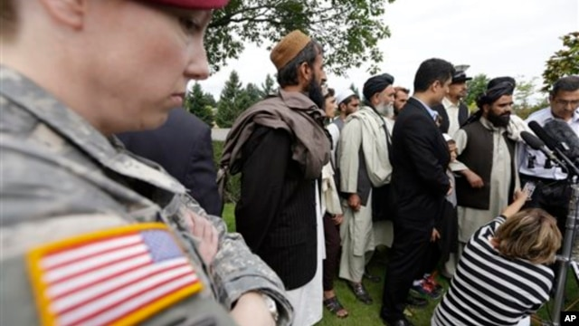 A U.S. soldier looks on as Afghan villagers, some of whom testified earlier in the week, speak through an interpreter with reporters, following a sentencing hearing for Staff Sgt. Robert Bales at Joint Base Lewis-McChord, Washington, Aug. 23, 2013.