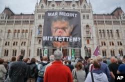 """ຊາຍຄົນນຶ່ງຖືປ້າຍທີ່ມີຮູບ ນາຍົກລັດຖະມົນຕີ Viktor Orban ທີ່ຂຽນວ່າ """"ຂ້າພະເຈົ້າໄດ້ເຮັດຫຍັງລົງໄປອີກແລ້ວ"""" ໃນຂະນະທີ່ທຳການປະທ້ວງ ໂດຍພັກຝ່າຍຄ້ານ ຕໍ່ຕ້ານນະໂຍບາຍຂອງທ່ານ Orban ກ່ຽວກັບພວກອົບພະຍົບ ໃນ Budapest, ຮົງກຣີ, 2 ຕຸລາ, 2016."""