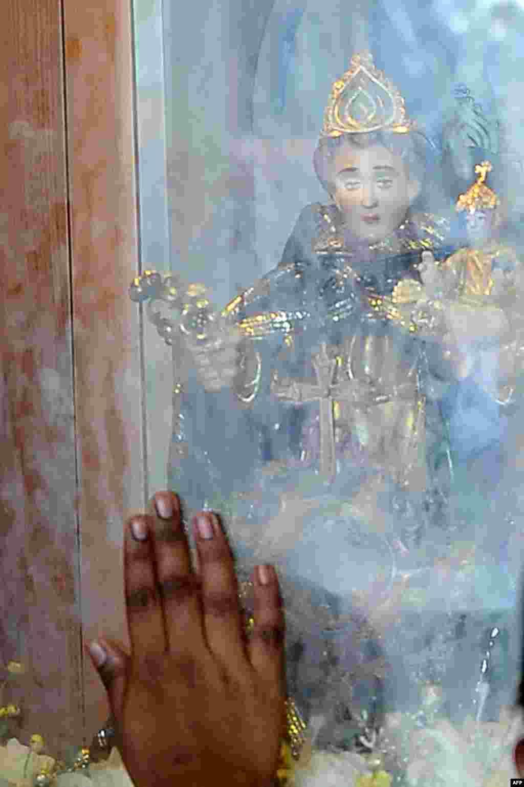 Một tín đồ Công Giáo Sri Lanka sờ tấm kính gần một hình tượng trong một thánh lễ tại một nhà thờ ở Colombo.