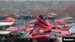 A migrant labourer sits under a quilt at an open space on a cold winter morning in the old quarters of Delhi December 19, 2013. REUTERS/Ahmad Masood (INDIA - Tags: SOCIETY ENVIRONMENT) - RTX16O7C