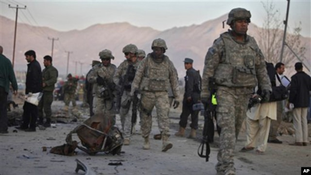 U.S. soldiers walk past the scattered parts of a vehicle used in an explosion on the outskirts of Kabul, Afghanistan, 12 Nov. 2010.