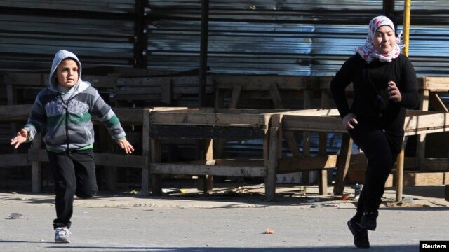 Children run fearing sniper fire in the northern Lebanese city of Tripoli, Jan. 20, 2014.