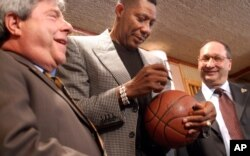 Brooklyn Bourough President Marty Markowitz, left, and CEO of Forest City Ratner Companies Bruce Ratner, right, pose with basketball legend Connie Hawkins as he autographs a basketball during a press conference in New York, Oct.14, 2003.