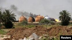 Asap membumbung dari tangki peyimpanan gas di pabrik pemrosesan gas untuk masak. Taji, utara Baghdad.