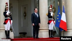 French President Francois Hollande stands outside the Elysee Palace as he waits for the arrival of a guest in Paris, May 7, 2013.