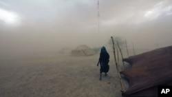 A Tuareg woman walks during a sandstorm in Ingal, Niger, September 18, 2011.