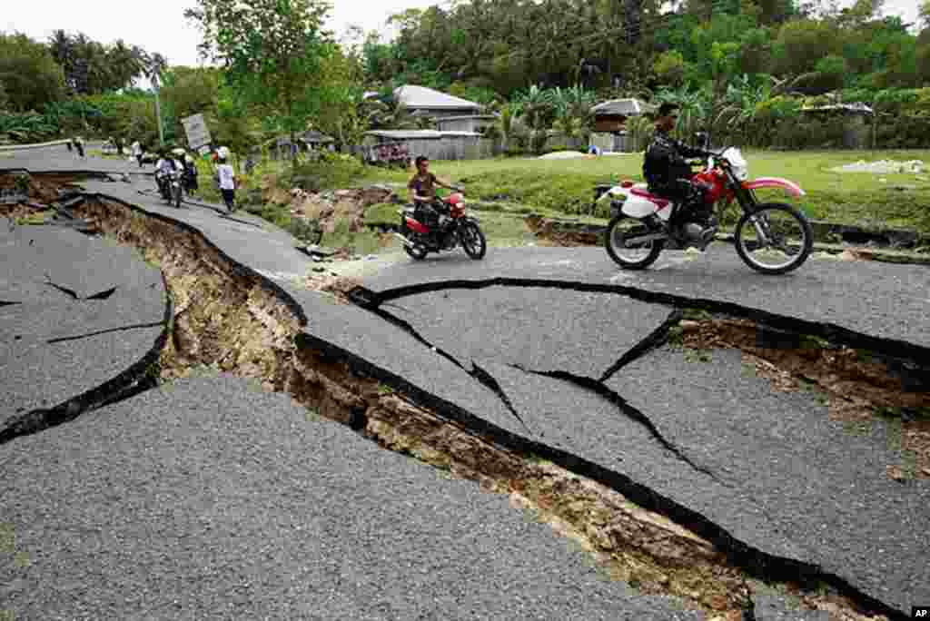 Soldiers on motorcycles past road destroyed by earthquake in La Libertad, Negros Oriental in central Philippines February 7, 2012. (Reuters)