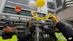 Police officers try to stop an anti-Beijing protester throwing a balloon with picture of jailed Chinese human rights activist Liu Xiaobo during a rally outside the Chinese liaison office in Hong Kong Thursday, Dec. 25, 2014.