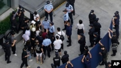 Investors are surrounded by police and security personnel as they try to enter the headquarters of the real estate developer Evergrande Group, Sept. 23, 2021, in Shenzhen, China.