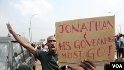 Seorang lelaki membawa poster menuntut mundurnya pemerintahan Presiden Jonathan, dalam aksi mogok masal memprotes kenaikan harga BBM di Lagos (11/1).