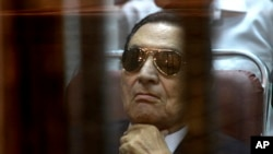 FILE-- In this Saturday, April 26, 2014 file photo, ousted Egyptian President Hosni Mubarak attends a hearing in his retrial over charges of failing to stop killings of protesters during the 2011 uprising that led to his downfall.