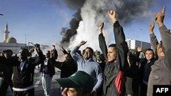 Gadafijeve pristalice u Tripoliju kliču u znak podrške libijskom lideru, dok se u pozadini vije dim posle eksplozije jedne cisterne za naftu
