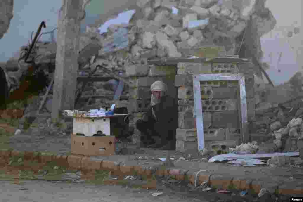 فروختن سیگار در میان ساختمان های خراب شده در حومه شهر حلب در سوریه.