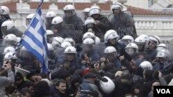 Policías antimotines contienen a los manifestantes frente al Parlamento.