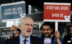 Britain's leader of the opposition Labour Party Jeremy Corbyn speaks to the media alongside demonstrators from multi-faith group 'Turn to Love' holding a vigil at New Zealand House in London, March 15, 2019.