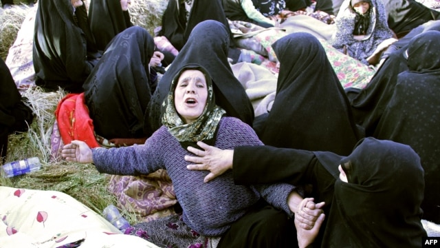Iranians mourn over the covered bodies of loved ones in the village Baje-Baj, near the town of Varzaqan, who were killed in twin earthquakes that hit northwestern Iran, August 12, 2012.