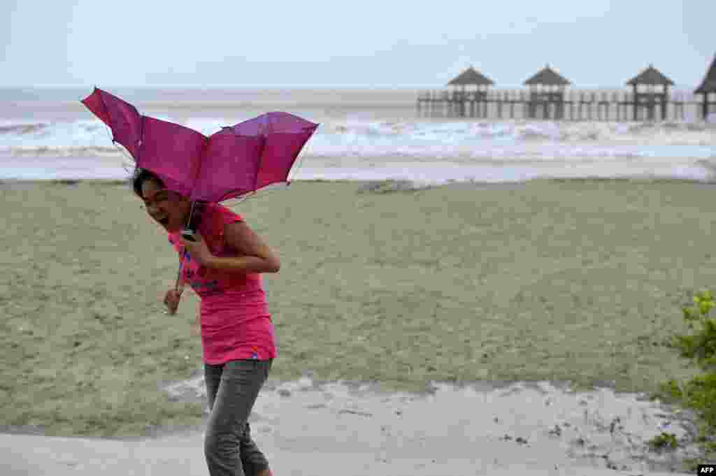A woman walks on the beach of Qinglan port, as strong wind breaks her umbrella in Wenchang, south China's Hainan province. China braced for a powerful super typhoon heading for its southern coast after the storm left a trail of destruction and at least 40 dead in the neighboring Philippines.