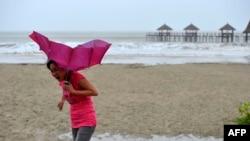 """超級颱風""""威馬遜""""經過中國海南文昌時,一名婦人持雨傘在沙灘走過。"""