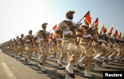 FILE - Members of the Iranian Revolutionary Guard march during a parade to commemorate the anniversary of the Iran-Iraq war (1980-88), in Tehran.