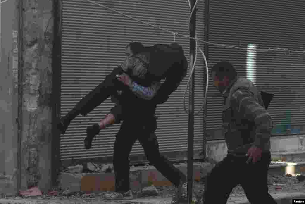 Azad Suriya Ordusunun döyüşçüləri yaralı yoldaşlarına yardım edir - Dəməşq
