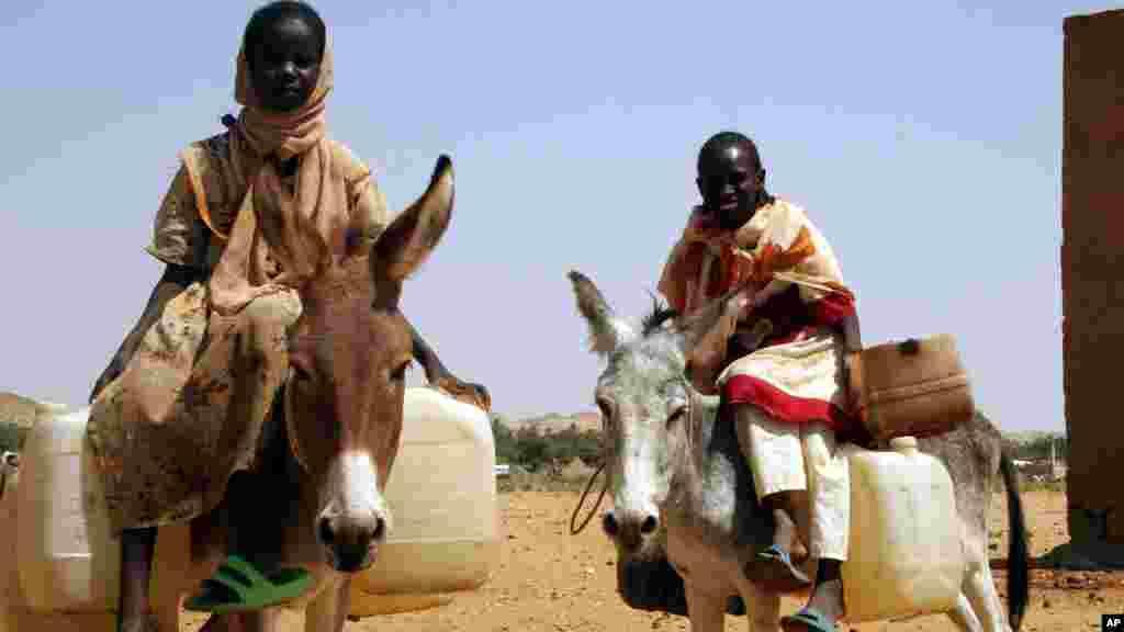 Deux jeunes filles quittent le camp de réfugiés de Fata Borno pour aller chercher de l'eau au Darfour, au Soudan le 14 octobre 2006.