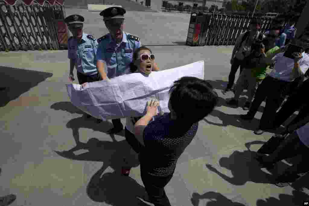 A Chinese woman, center with sunglasses, protests outside the Jinan Intermediate People's Court in Jinan, eastern China's Shandong province, August 21, 2013.