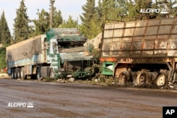 FILE - This image provided by the Syrian anti-government group Aleppo 24 news, shows damaged trucks carrying aid, in Aleppo, Syria, Sept. 20, 2016.