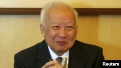 Cambodian King Norodom Sihanouk holds a glass during a meeting with Chinese State Councilor Dai Bingguo (not seen) in Beijing, October 30, 2006.