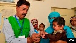 بلوچستان میں پولیو سے بچاؤ کی مہم کے دوران محکمہ صحت کا ایک کارکن اپنے کام میں مصروف ہے۔ فائل فوٹو