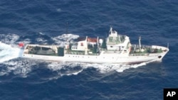 In this photo released by Japan Coast Guard, a Chinese fisheries patrol boat sails near disputed islands, called Senkaku in Japan and Diaoyu in China, in the East China Sea Tuesday, Sept. 18, 2012.
