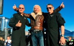 "Richard Branson center celebrates with pilots Rick ""CJ"" Sturckow (L), and Mark ""Forger"" Stucky (R), after Virgin Galactic's tourism spaceship climbed more than 50 miles high above California's Mojave Desert on Dec. 13, 2018."