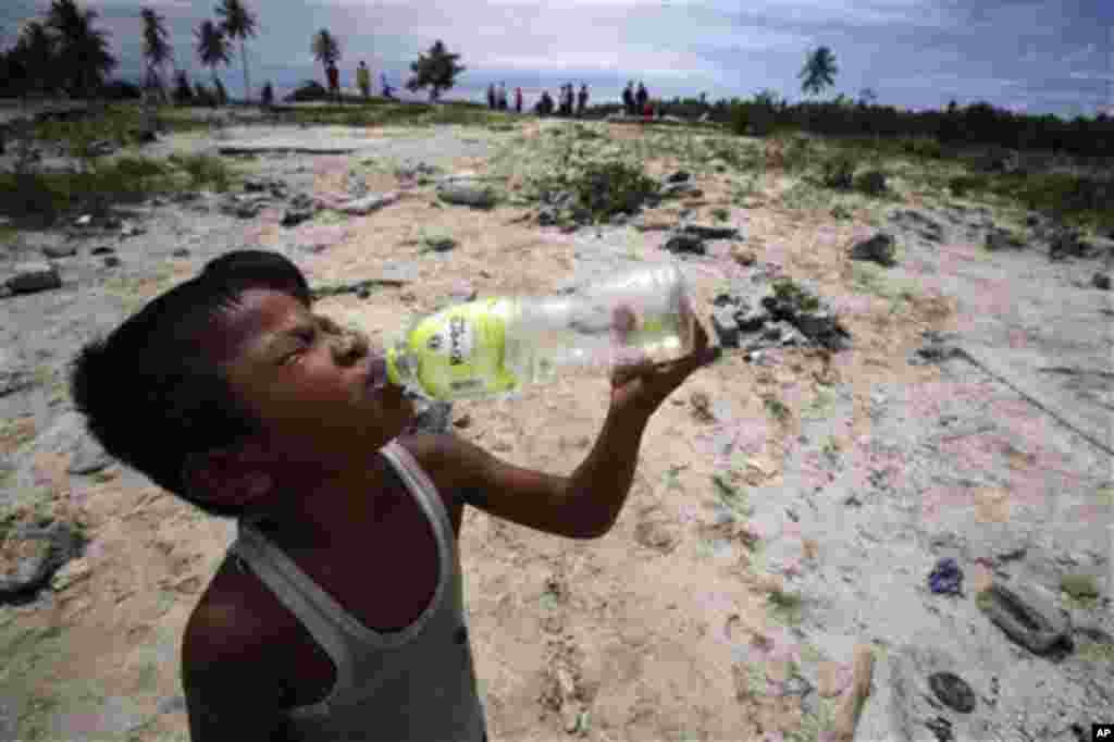 A boy tsunami survivor drinks water at an area affected by Monday's earthquake-triggered tsunami at Parorogat village, Pagai island, West Sumatra, Indonesia, on Thursday, Oct. 28, 2010. (AP Photo/Achmad Ibrahim)