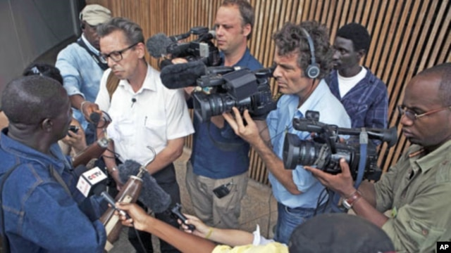 Members of the media surround war double-amputee Alhaji Jusu Jarka outside the Special Court for Sierra Leone, after a live broadcast of the verdict by a UN-backed court in the Hague convicting former Liberian president Charles Taylor of war crimes, in ca