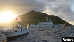 FILE - Chinese marine surveillance ship Haijian No. 51 (C) sails near Japan Coast Guard vessels (R and L) and a Japanese fishing boat (front 2nd L) as Uotsuri island, one of the disputed islands, called Senkaku in Japan and Diaoyu in China, is in the background, July 1, 2013.
