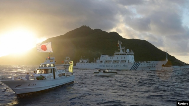 Chinese marine surveillance ship Haijian No. 51 (C) sails near Japan Coast Guard vessels (R and L) and a Japanese fishing boat (front 2nd L) as Uotsuri island, one of the disputed islands, called Senkaku in Japan and Diaoyu in China, is in background, Jul