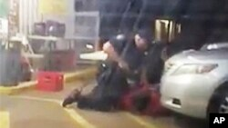 FILE - Image made from video shows Alton Sterling being restrained by two Baton Rouge police officers, one holding a gun, outside a convenience store in Baton Rouge, Louisiana, July 5, 2016, before one of the officers shot and killed Sterling, a black man who had been selling CDs outside the store, while he was on the ground.