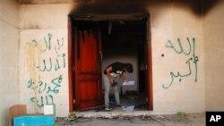 去年美國駐利比亞城市班加西領館遇襲後﹐一名男子檢視地上得文件。