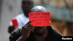 FILE - A Congolese opposition party supporter displays a red card against President Joseph Kabila in Kinshasa, Democratic Republic of the Congo, Dec. 19, 2016.