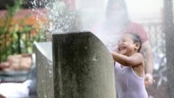 New York'ta fıskiye sularıyla serinlemeye çalışan bir çocuk