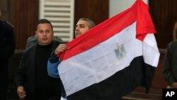 محمد فهمی خبرنگار کانادایی شبکه الجزیره که پس از جلسه دادگاه در قاهره، پرچم مصر را در دست گرفته است – ۲۳ بهمن ۱۳۹۳