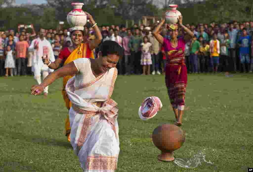 An Indian tribal woman reacts after an earthen pot filled with water falls off her head during a 100-meter sprint event with water pots on heads, in the Suwori Tribal festival in Boko.