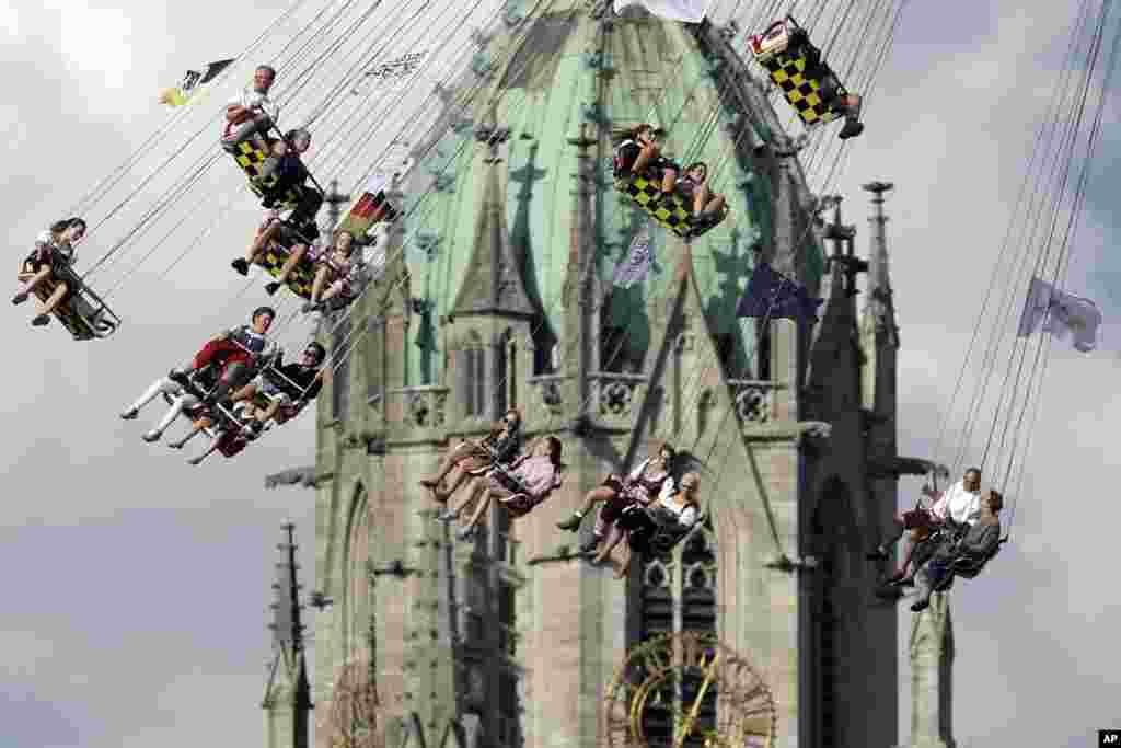 People ride a swing in front of St. Paul's church at the 183rd Oktoberfest beer festival in Munich, Germany.