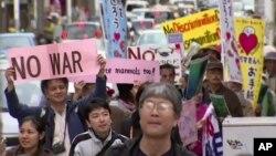 Manifestantes marchan en contra del traslado de la base de Okinawa a otro lugar de esa isla.