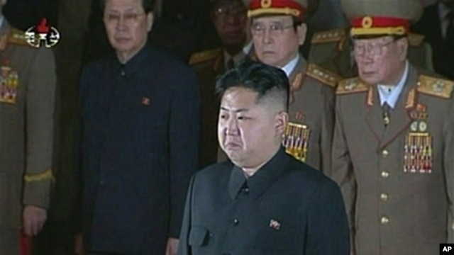 New North Korean ruler Kim Jong Un (front) pays his respects to his father and former leader Kim Jong Il, lying in state at the Kumsusan Memorial Palace in Pyongyang, December 20, 2011.