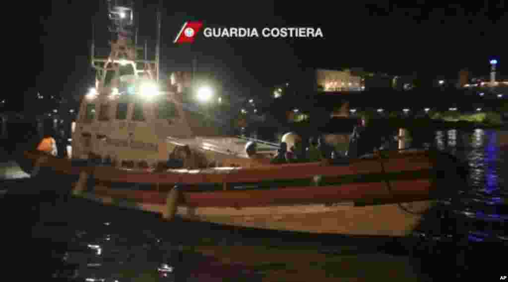 This image from video shows survivors of a ship that sank being transported on an Italian Coast Guard vessel as it arrives at port, Lampedusa, Italy, Oct. 3, 2013. (Italian Coast Guard)