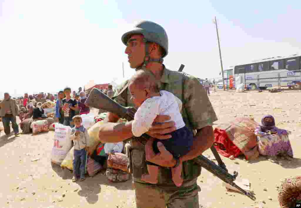 A Turkish soldier holds a lost baby while he looks for the mother, as thousands of new Syrian refugees from Kobani arrive at the Turkey-Syria border crossing of Yumurtalik near Suruc, Turkey.