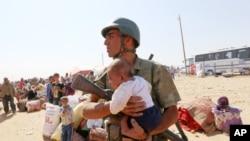 Một binh sĩ Thổ Nhĩ Kỳ bế một em bé bị lạc trong khi đi tìm bà mẹ. Hàng ngàn ngượi tị nạn chạy từ thị trấn Kobani đến cửa khẩu biên giới Syria-Thổ Nhĩ Kỳ, 2/10/14