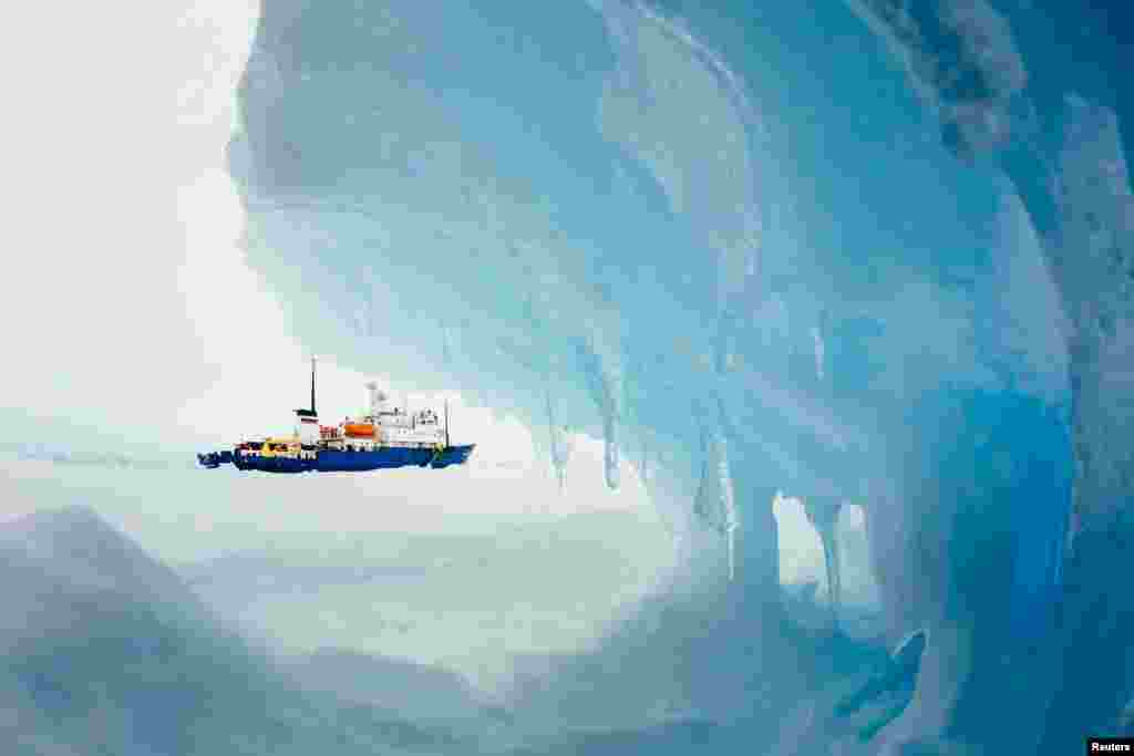The MV Akademik Shokalskiy is seen stranded in ice in Antarctica, Dec. 29, 2013. An Antarctic blizzard has halted an Australian icebreaker's bid to reach the Russian ship trapped for a week with 74 people onboard, rescuers said on Monday.