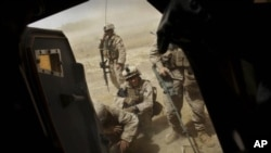 United States Marines from Bravo Company of the 1st Battalion of the 2nd Marines take cover outside their vehicle as a medevac helicopter leaves the scene with a wounded colleague following an IED strike near Musa Qaleh, in northern Helmand Province, sout