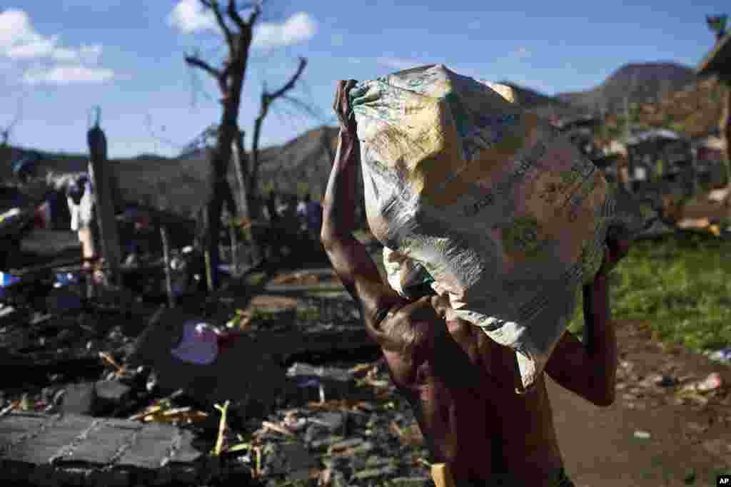 A Typhoon Haiyan survivor carries a bag of his recovered belongings in the ruins of his rural neighborhood on the outskirts of Tacloban, Philippines, Nov. 18, 2013.